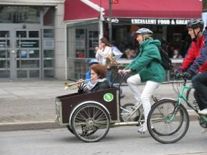 Kia Andreasson cyklar mp-cykelvagnen med en trumpetare i (som var del av ett jättesvängigt cyklande klezmerband!)
